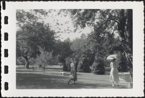 Two women (one with parasol) walking on grounds