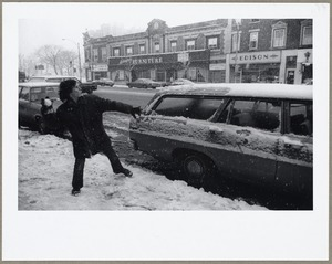 Boy throwing snowball, Mass. Ave., Arlington Center