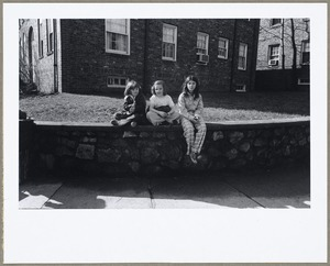Children seated on stone wall waiting for bus on Broadway