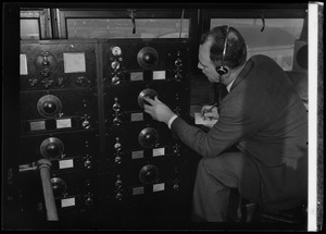 American Airlines traffic control tower. Man turning dial on panel