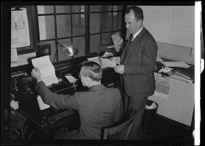American Airlines traffic control tower. Two men at examining teletype output