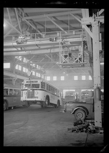 Bus in a garage lifted by a hoist