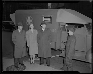 Clapper, Crowley, and model talking to a man in front of ambulance