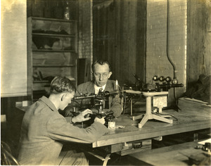 Dr. Edgar D. Tillyer at table with assistant working at American Optical Southbridge