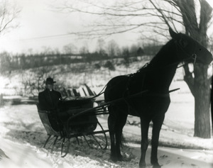 Bill McGuire in a horse-drawn sleigh