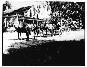 Stagecoach in front of store in center of town