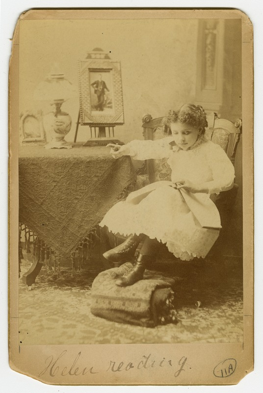 Helen Keller, as a young girl, reading