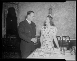 A woman and man talking near a dining table