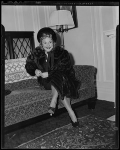 Sonja Henie on arrival seated on couch