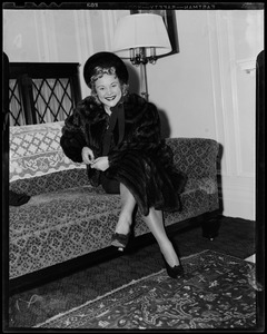 Sonja Henie on arrival seated on a couch
