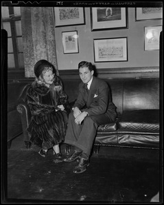 Sonja Henie on couch, talking with a man