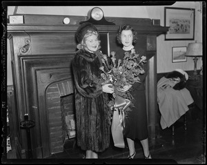 Sonja Henie holding flowers and posing with another woman in front of a fireplace