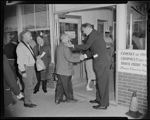 George C. Lodge shaking a man's hand as he walks into the Raytheon Missile and Space Division Andover Plant building