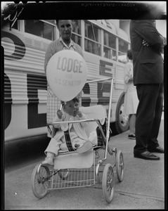 Young child in a stroller holding a Lodge for U.S. Senator balloon
