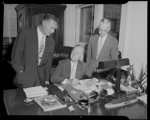 City Clerk Walter J. Malloy, right, and Atty. Joseph J. Gottleib, representing Sears Roebuck, look on after Mayor Hynes signs the bill authorizing the sale of city-owned land in Fenway to Sears Roebuck and Co.