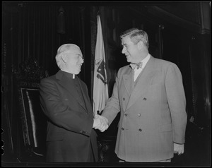 Thomas P. O'Neill shaking hands with a clergyman in front of a flag
