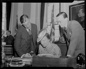 Governor Saltonstall and Prince Bernhard look on while Princess Juliana, seated, signs a book