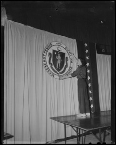 A woman hangs the Massachusetts GOP. seal for a ceremony during President Dwight Eisenhower's Boston visit