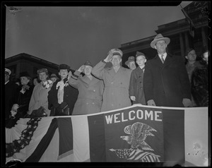 General Eisenhower salutes from a stand with welcome banner