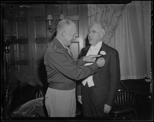 General Eisenhower pinning a flower onto Boston University President Daniel L. Marsh's jacket