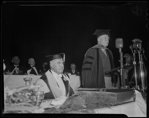General Eisenhower in robes and cap at podium with Boston University President Daniel Marsh seated at his right
