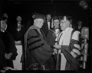 General Eisenhower in a robe and cap, shaking hands with Boston University President Daniel L. Marsh