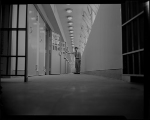 Prison guard standing at a row of cells