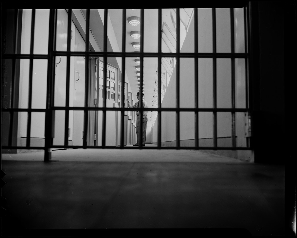 Prison guard standing at a row of cells seen through a gate
