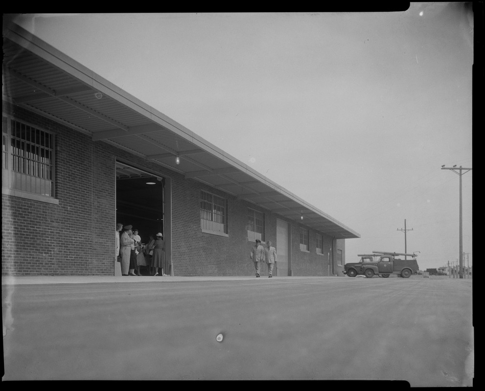 Exterior view of the Walpole Prison, people can be seen through an opening and outside