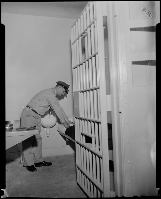 Guard Raymond Mazetis fixing the bed in a cell