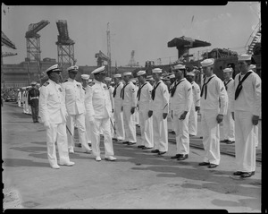 Captain G.T. Ferguson, Captain J.F. Enright and Lefteris Lavrakas walk by a row of sailors during the U.S.S. Boston change of command ceremonies
