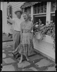 Walter and Madeline Gibbons standing outside of a house