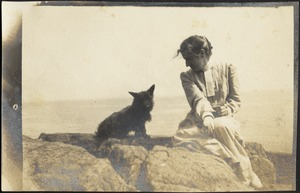 "Helen Stevens Coolidge sitting with dog (possibly ""Ping"") at beach"