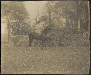Ashdale Farm. Gertrude S. Kunhardt on horseback in front of stone wall.