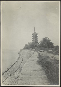 View of sea wall with walkway, temple in distance