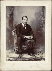 Studio portrait of U. S. Consul Adelbert S. Hay seated holding hat and cigarette