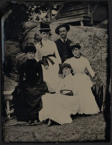 4 women and 1 man sitting on rocks near cabin