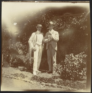 Two well-dressed gentlemen standing in garden