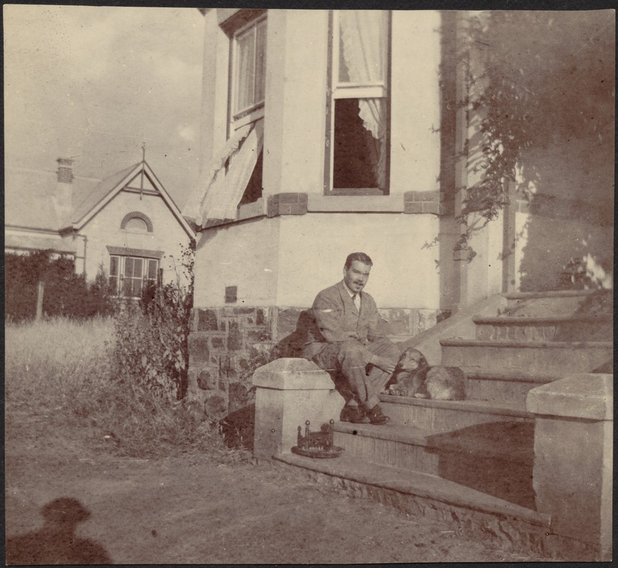 Adelbert S. Hay sitting on steps with small dog in front of house