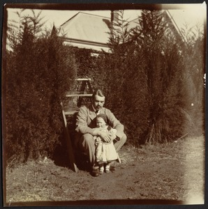 Consul Adelbert S. Hay sitting on step ladder holding small child
