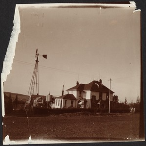White house with windmill and small water tanks