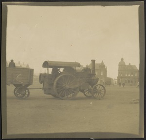 Steam car on street towing another car, city buildings in distance