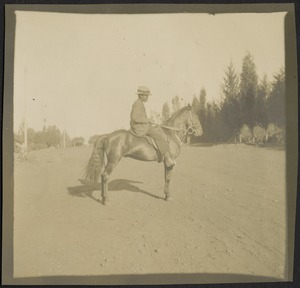 African boy w/hat on horseback