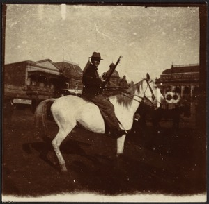 Calvary office holding rifle on horseback, riding in city street