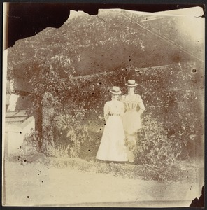 Two women standing in garden