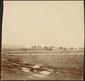 Distant view of camp, possibly a prison camp; lumber in foreground