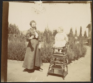 Woman standing next to small child in wooden high chair in garden