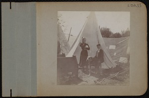 A boy and girl in front of tents
