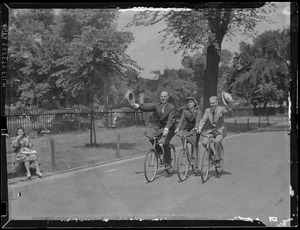 Two men and uniformed woman riding bikes