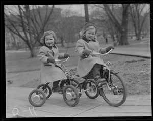 2 girls on tricycles